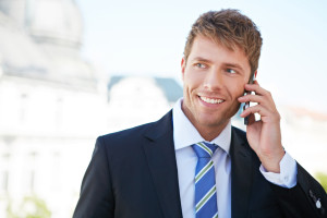 Geschäftsmann in Stadt am Tag telefoniert lachend mit Smartphone